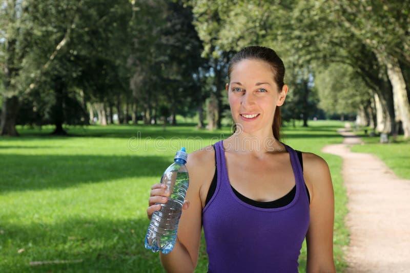 Αθλητική νέα γυναίκα με ένα μπουκάλι νερό στοκ φωτογραφία με δικαίωμα ελεύθερης χρήσης