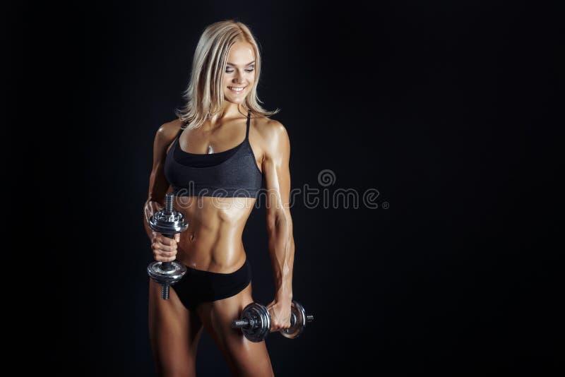 Αθλητική νέα γυναίκα που κάνει μια ικανότητα workout με τα dumbbels στοκ φωτογραφία με δικαίωμα ελεύθερης χρήσης