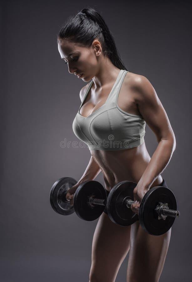 Αθλητική νέα γυναίκα που κάνει μια ικανότητα workout με τους αλτήρες στο γ στοκ εικόνες