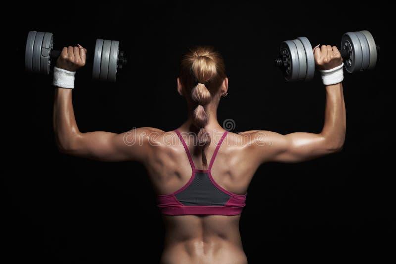 Αθλητική νέα γυναίκα bodybuilder με τους αλτήρες ξανθό κορίτσι με τους μυς στοκ εικόνες