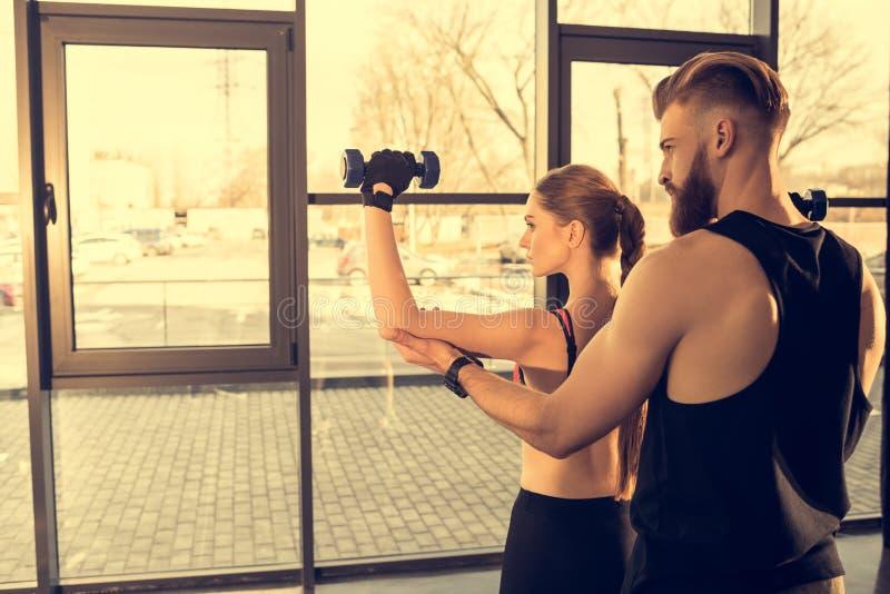 Αθλητικός άνδρας που εκπαιδεύει τη νέα φίλαθλη γυναίκα με τους αλτήρες στη γυμναστική στοκ εικόνες με δικαίωμα ελεύθερης χρήσης