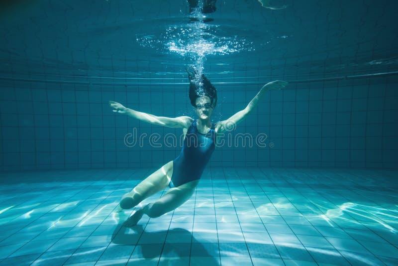 Αθλητικός κολυμβητής που χαμογελά στη κάμερα υποβρύχια στοκ φωτογραφία