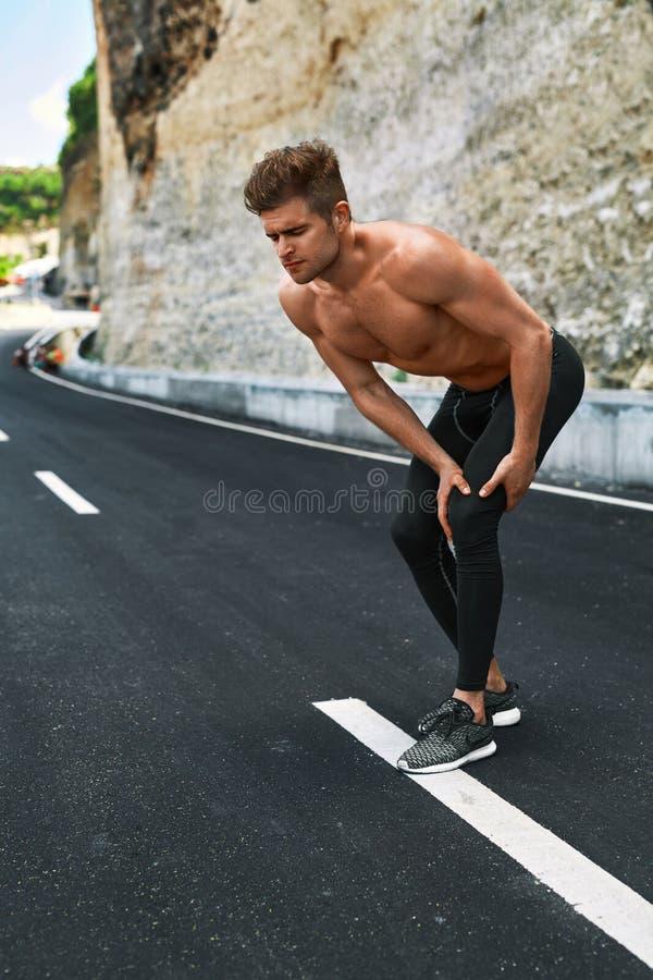 Αθλητικός τραυματισμός Τραυματισμένο άτομο πόδι κατά τη διάρκεια να τρέξει υπαίθρια τραυματισμών τρέχοντας αθλητισμός δρομέων πόν στοκ εικόνα