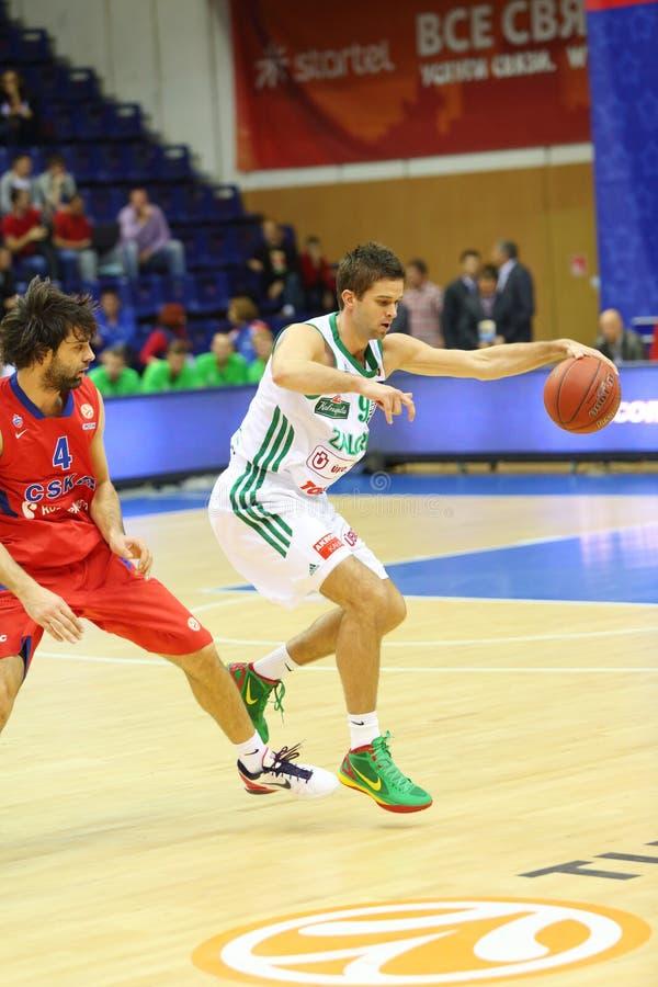 Αθλητικός τύπος από την ομάδα Zalgiris (Λιθουανία, στο λευκό) με την καλαθοσφαίριση στοκ εικόνα