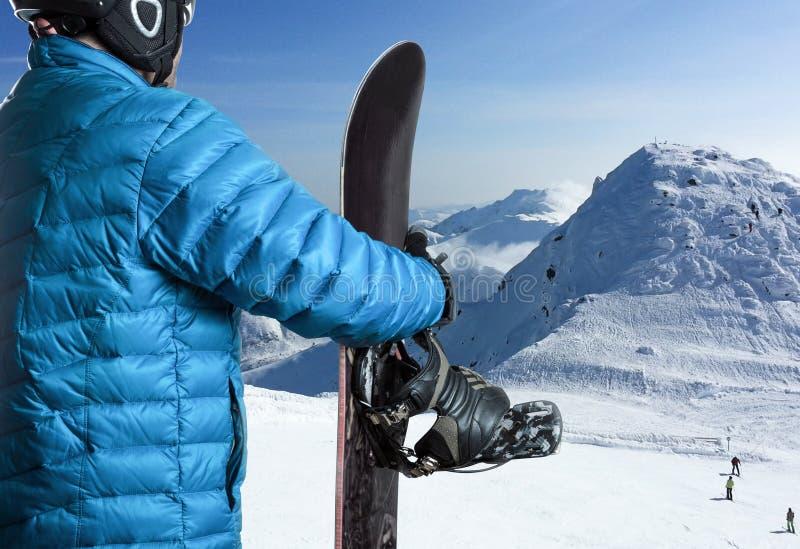 Αθλητικός τύπος με το σνόουμπορντ που στέκεται στα βουνά στοκ εικόνα