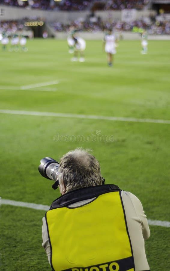 Αθλητικός φωτογράφος που εξετάζει τη δράση στοκ φωτογραφία με δικαίωμα ελεύθερης χρήσης