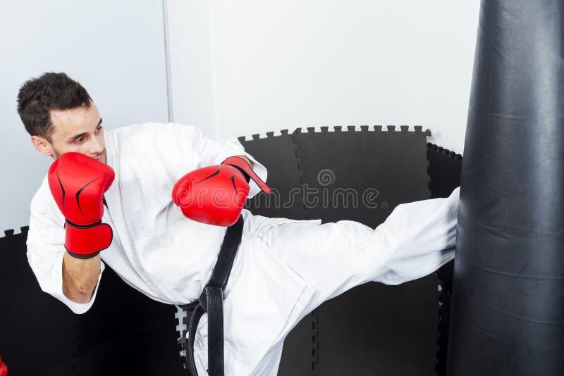 Αθλητικός karate μαχητής που δίνει ένα ισχυρό λάκτισμα ποδιών σε ένα βαρύ β στοκ εικόνα