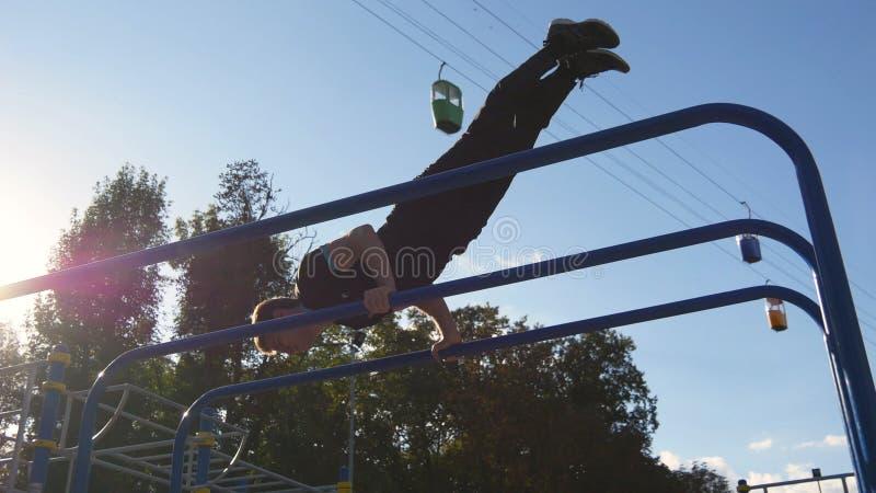 Αθλητικό άτομο που κάνει τα στοιχεία γυμναστικής στο φραγμό στο πάρκο πόλεων Ο αρσενικός αθλητικός τύπος εκτελεί τις ασκήσεις δύν στοκ εικόνες