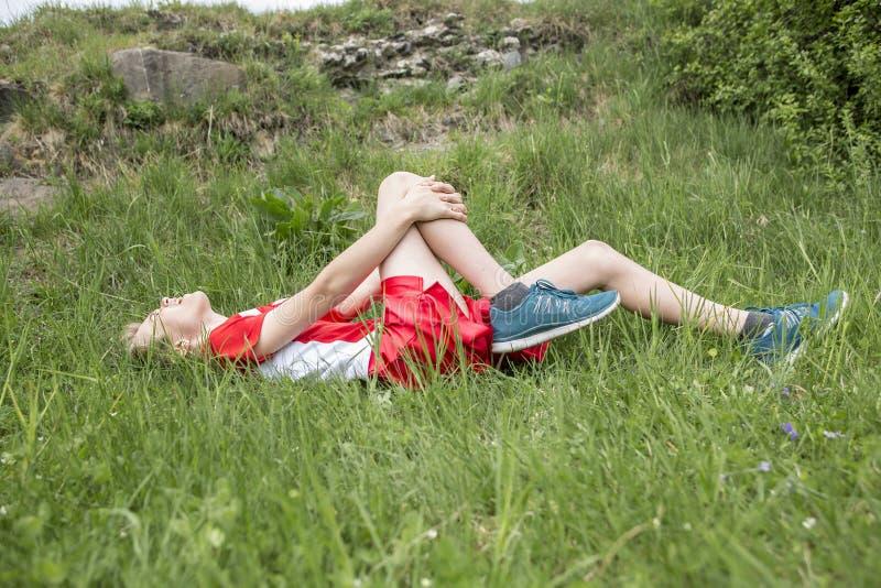 Αθλητικό αγόρι που κρατά το επίπονο τραυματισμένο γόνατό της στοκ εικόνα