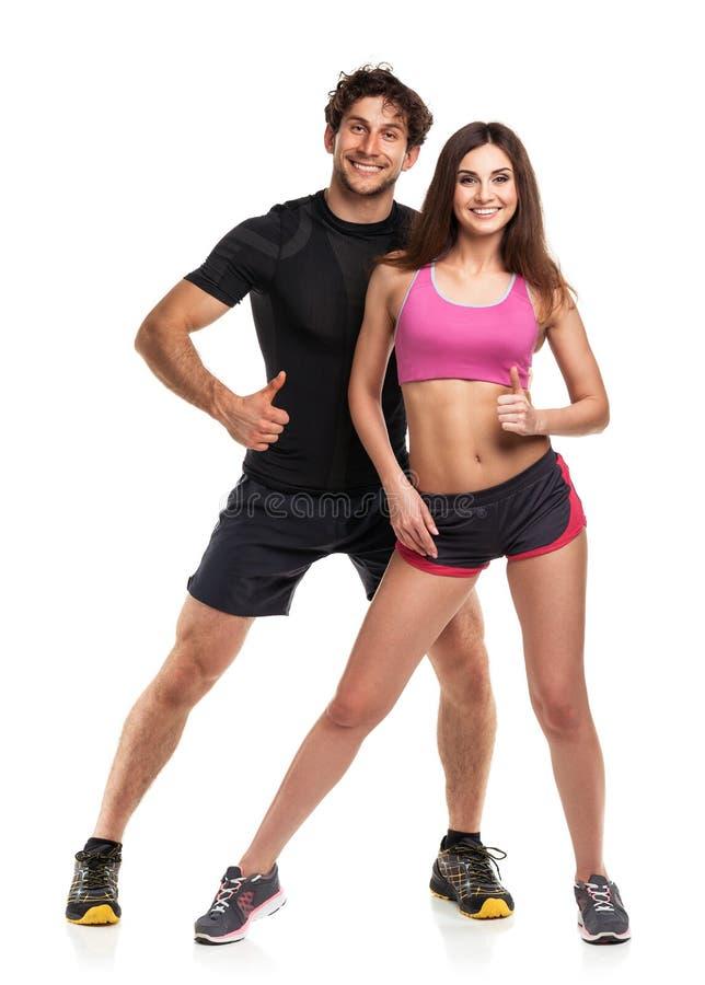 Αθλητικό ζεύγος - άνδρας και γυναίκα με τον αντίχειρα επάνω στο λευκό στοκ εικόνες