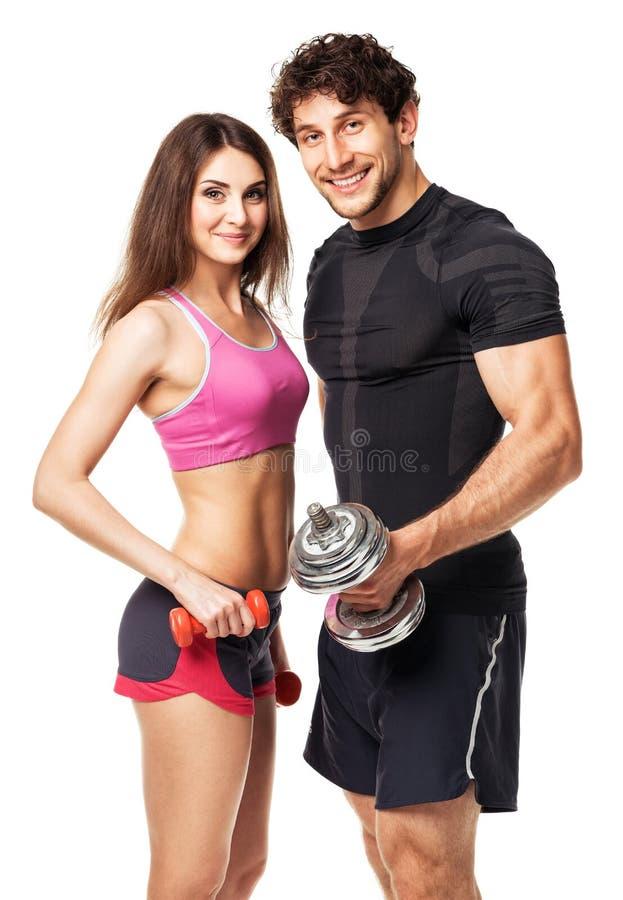 Αθλητικό ζεύγος - άνδρας και γυναίκα με τους αλτήρες στο λευκό στοκ φωτογραφίες