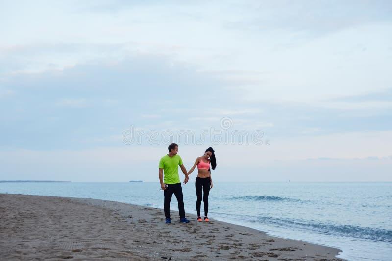 Αθλητικό ζεύγος που περπατά κατά μήκος της παραλίας που στηρίζεται μετά από το workout στοκ εικόνες