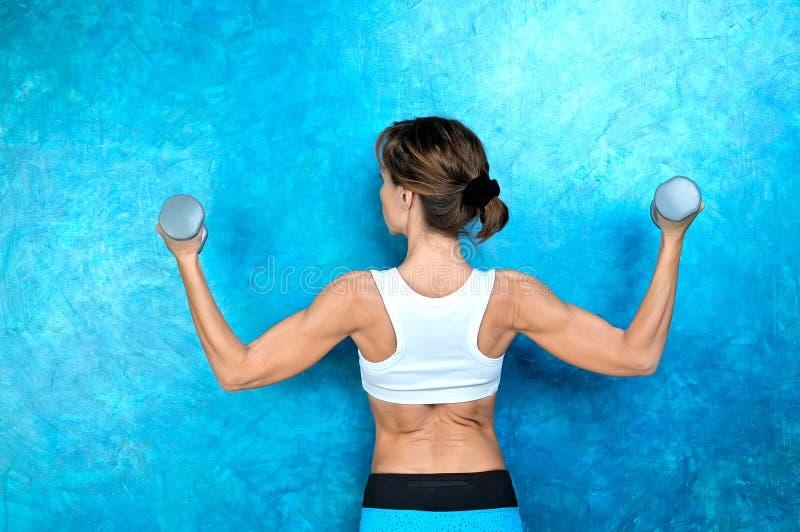 Αθλητικό κορίτσι που κάνει workout την άσκηση με τους αλτήρες Βλαστός στούντιο στοκ εικόνες