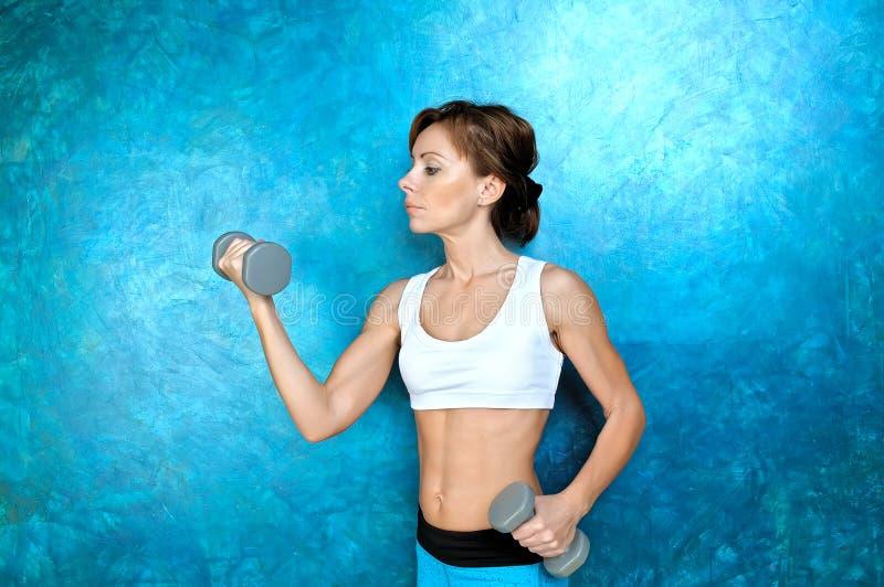 Αθλητικό κορίτσι που κάνει workout την άσκηση με τους αλτήρες Βλαστός στούντιο στοκ εικόνα