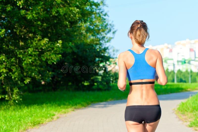 Αθλητικό κορίτσι σε μια κορυφή και τα σορτς που τρέχουν στο δρόμο στο πάρκο στοκ φωτογραφία με δικαίωμα ελεύθερης χρήσης