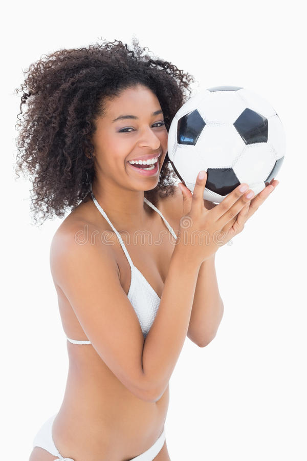 Αθλητικό κορίτσι στο άσπρο ποδόσφαιρο εκμετάλλευσης μπικινιών στοκ εικόνα