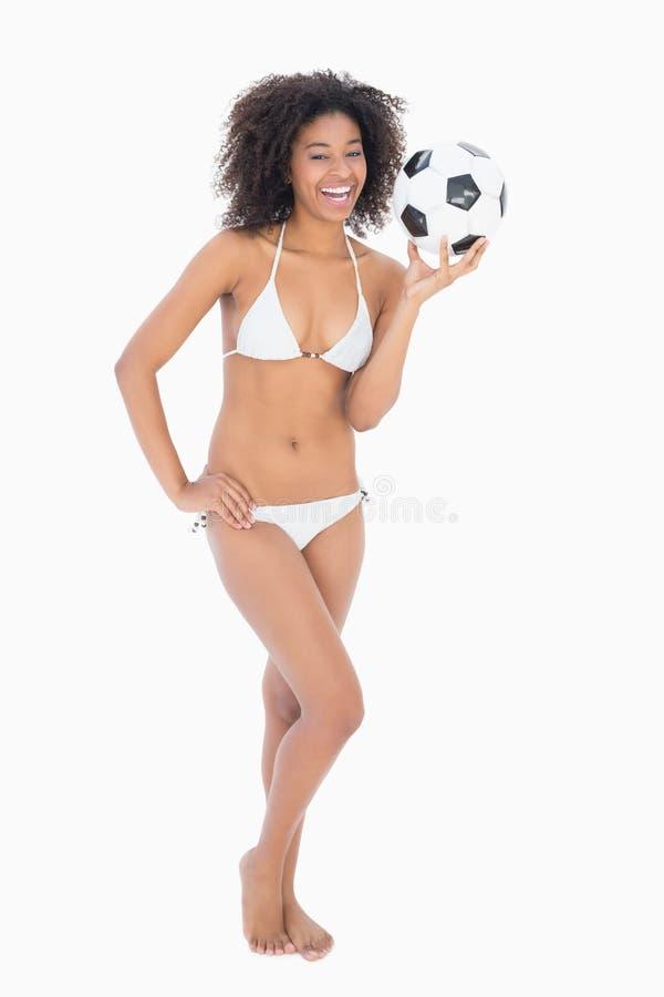Αθλητικό κορίτσι στο άσπρο ποδόσφαιρο εκμετάλλευσης μπικινιών στοκ φωτογραφίες με δικαίωμα ελεύθερης χρήσης