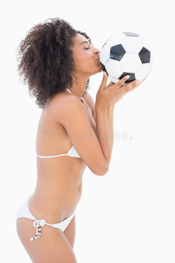 Αθλητικό κορίτσι στο άσπρο ποδόσφαιρο φιλήματος μπικινιών στοκ εικόνα
