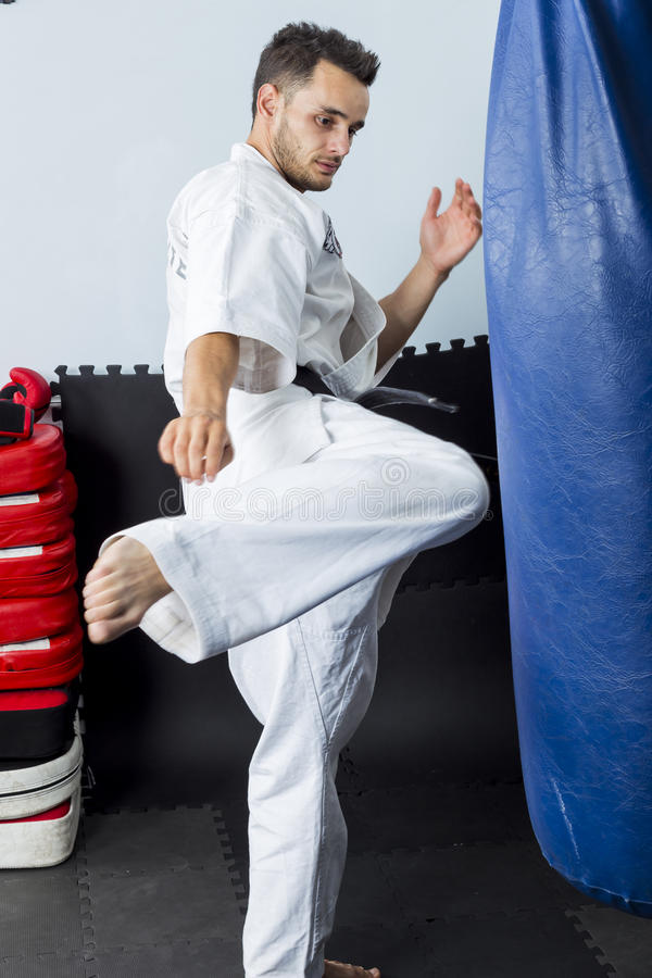 Αθλητικό μαύρο karate ζωνών που δίνει ένα ισχυρό λάκτισμα γονάτων στοκ εικόνες