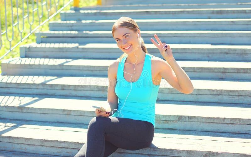 Αθλητισμός και έννοια ικανότητας - η όμορφη χαμογελώντας νέα γυναίκα ακούει τη μουσική στο smartphone στην πόλη στοκ φωτογραφία με δικαίωμα ελεύθερης χρήσης
