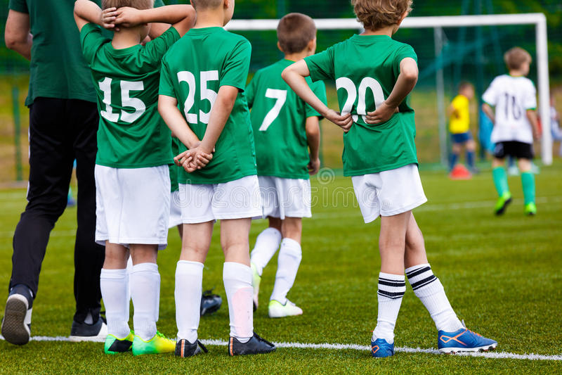 Αθλητισμός νεολαίας προγύμνασης Νέα αγόρια με το προπονητή ποδοσφαίρου στην πίσσα στοκ εικόνες
