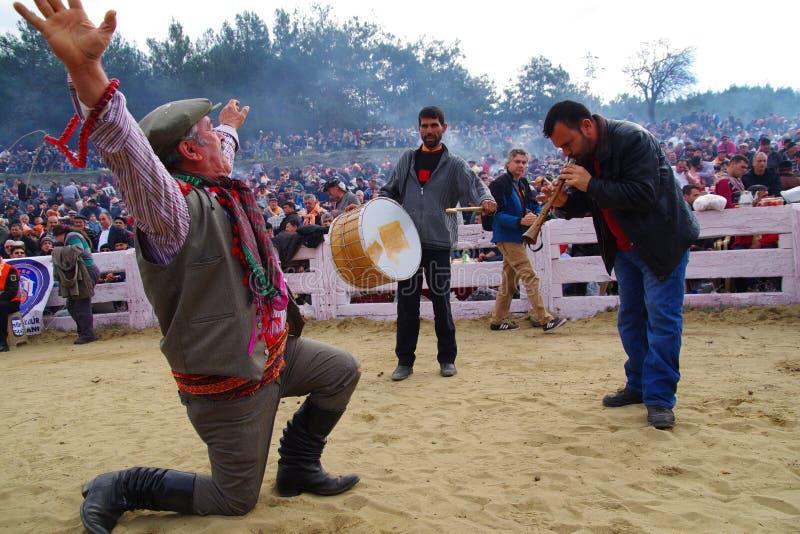 Αιγαίο λαϊκό άτομο χορευτών που εκτελεί το χορό από ένα γόνατο στο έδαφος με έναν τυμπανιστή και μια σάλπιγγα στοκ εικόνες