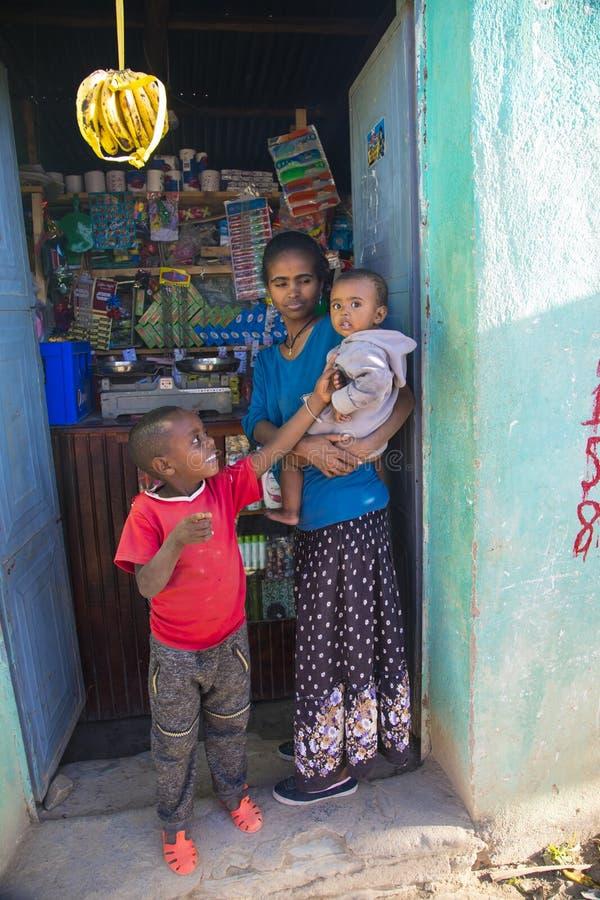 Αιθιοπική γυναίκα και τα παιδιά της σε την λίγο μανάβικο στοκ εικόνα