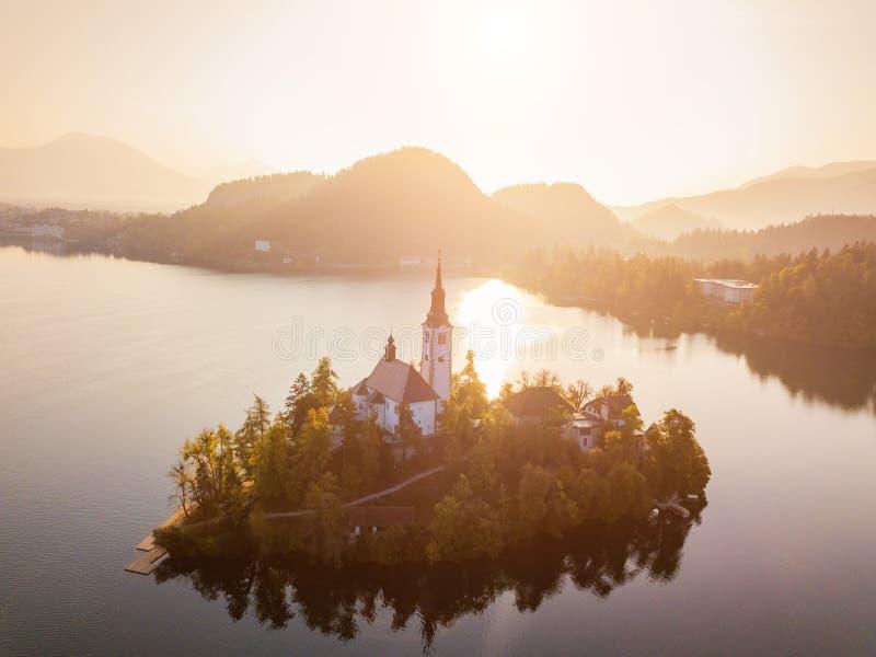 Αιμορραγημένη λίμνη με την εκκλησία προσκυνήματος της υπόθεσης της Μαρίας στην ανατολή εναέρια όψη στοκ εικόνα με δικαίωμα ελεύθερης χρήσης