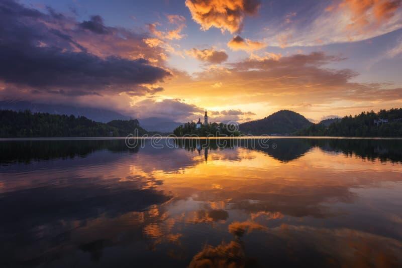 αιμορραγημένη λίμνη Όμορφη ανατολή πέρα από την αιμορραγημένη λίμνη με τη μικρή εκκλησία προσκυνήματος Διασημότερα σλοβένικα λίμν στοκ εικόνες