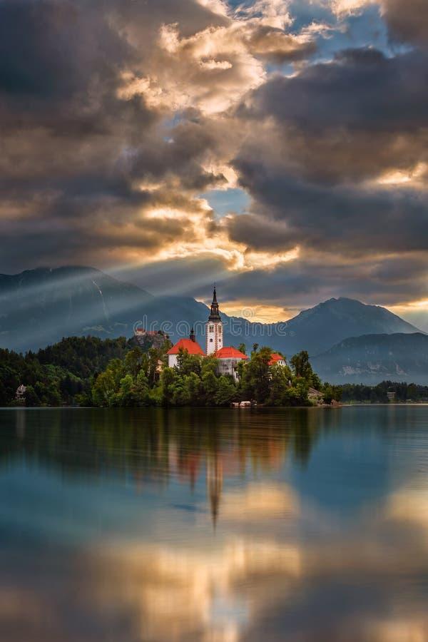 Αιμορραγημένος, Σλοβενία - η χρυσή ανατολή στη λίμνη αιμορράγησε Blejsko Jezero με την εκκλησία προσκυνήματος της υπόθεσης της Μα στοκ φωτογραφία με δικαίωμα ελεύθερης χρήσης