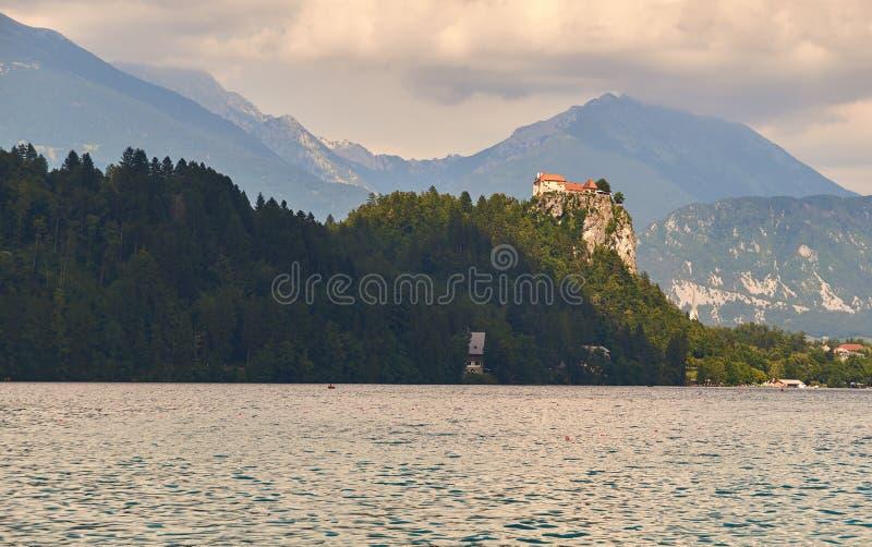 Αιμορραγημένο κάστρο σε έναν απότομο βράχο πέρα από τη λίμνη στοκ εικόνες