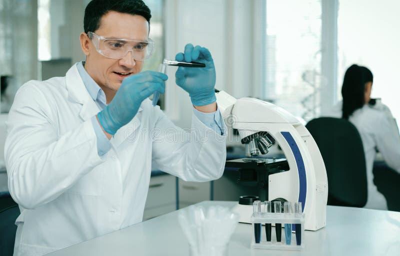 Αινιγματικός επαγγελματίας που κάνει το χημικό πείραμα στοκ εικόνα