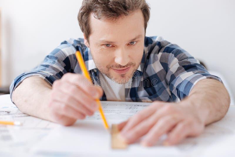 Αινιγματικός μηχανικός που εξετάζει το κίτρινο μολύβι στοκ εικόνα