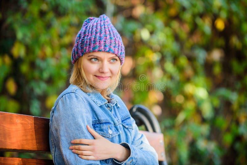 Αισθανθείτε άνετος αυτήν την πτώση με το μαλακό και θερμό μοντέρνο καπέλο Η γυναίκα κάθεται το υπόβαθρο φύσης πάρκων πάγκων Πλεκτ στοκ φωτογραφίες