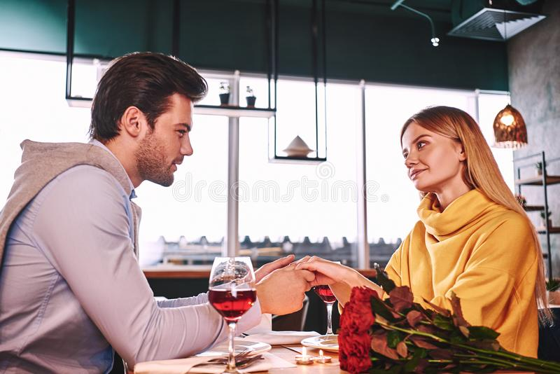 Αισθησιακές στιγμές Χέρια εκμετάλλευσης νεαρών άνδρων της φίλης του στο εστιατόριο στοκ φωτογραφίες