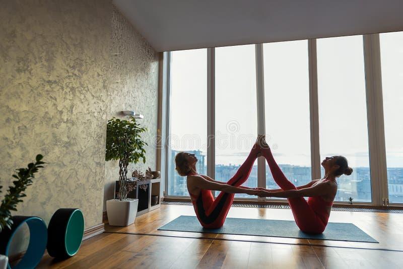 Αισθησιακές δύο γυναίκες που κάθονται στην αθλητική θέση στοκ εικόνες