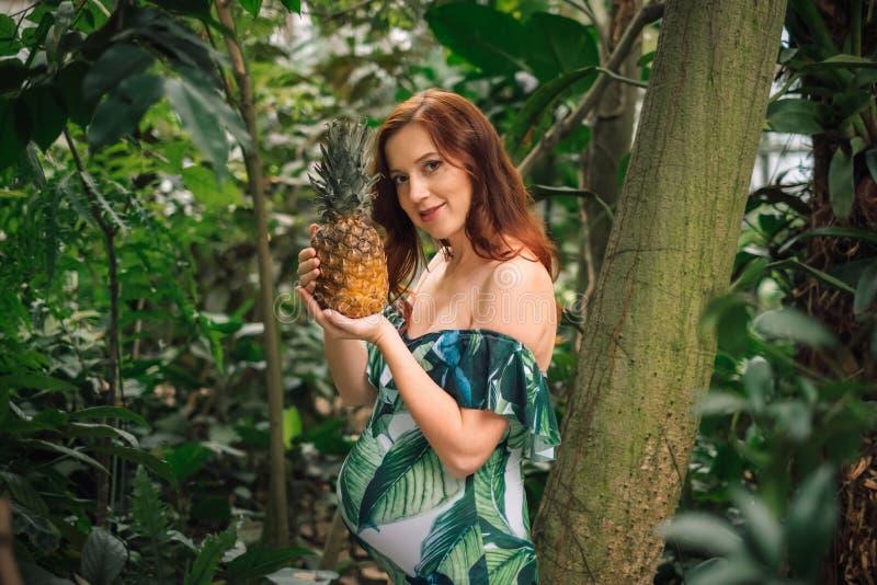Αισθησιακή έγκυος καυκάσια γυναίκα με έναν ανανά σε ένα δάσος στοκ φωτογραφία με δικαίωμα ελεύθερης χρήσης
