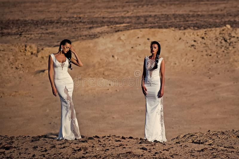 Αισθησιακή γυναίκα Δύο κορίτσια στα άσπρα φορέματα που θέτουν στους αμμόλοφους άμμου στοκ εικόνες