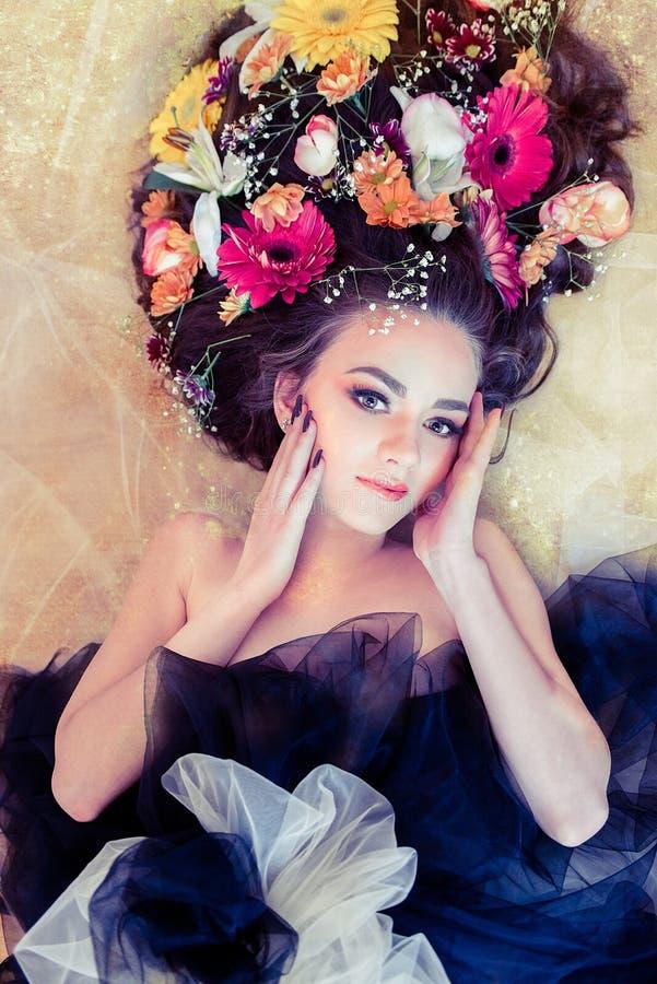 Αισθησιακή γυναίκα με τα λουλούδια στην τρίχα της σχετικά με το πρόσωπό της στο χρυσό στοκ φωτογραφίες με δικαίωμα ελεύθερης χρήσης