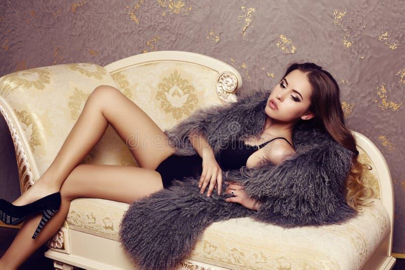 Αισθησιακή γυναίκα με την πολυτελή σγουρή τρίχα που φορά το κομψό παλτό γουνών στοκ φωτογραφία