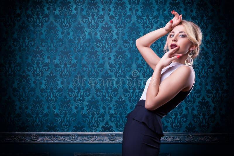 Αισθησιακή γυναίκα στο μπλε εκλεκτής ποιότητας υπόβαθρο στοκ φωτογραφίες