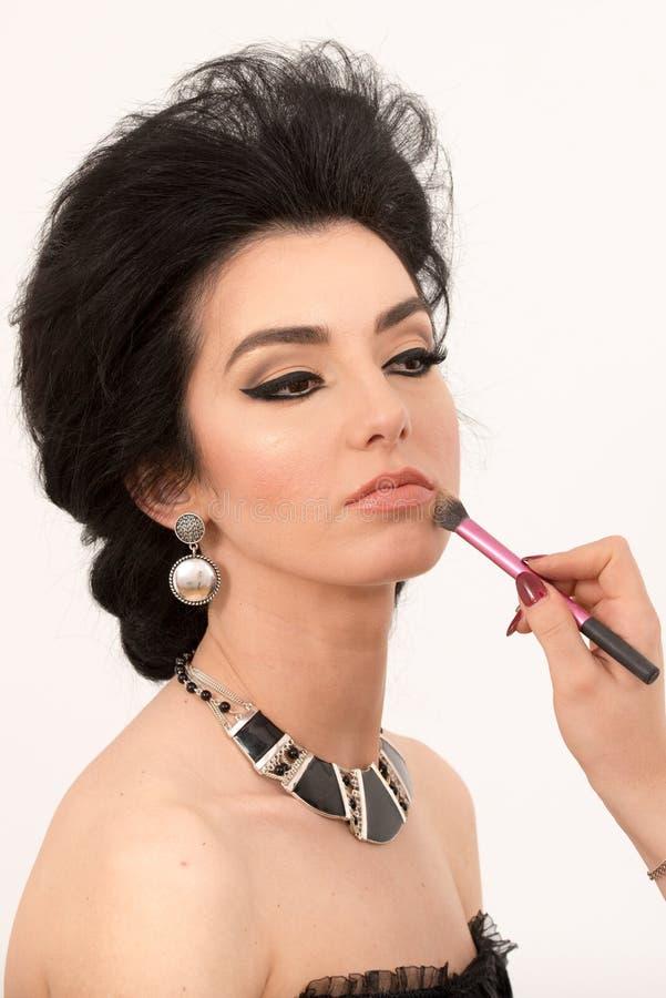 Αισθησιακή γυναίκα brunette αναδρομική που ορίζει κατά τη διάρκεια του ρετουσαρίσματος makeup στο whi στοκ εικόνα