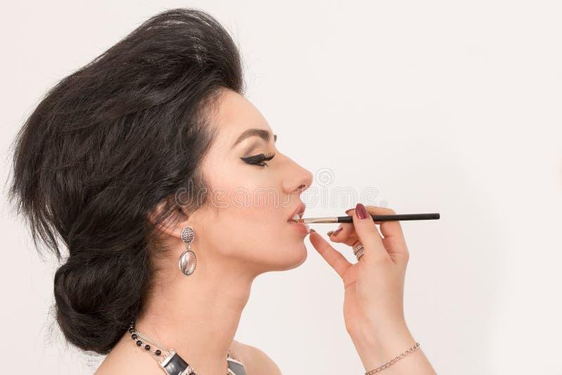 Αισθησιακή γυναίκα brunette αναδρομική που ορίζει κατά τη διάρκεια του χειλικού ρετουσαρίσματος ο makeup στοκ εικόνα με δικαίωμα ελεύθερης χρήσης