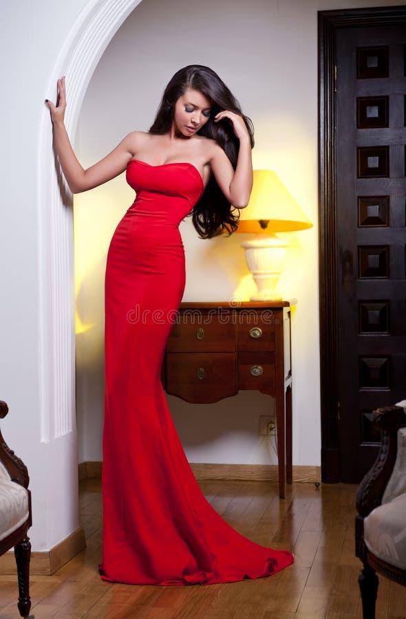 Αισθησιακή κομψή νέα γυναίκα στο κόκκινο φόρεμα και τον εσωτερικό πυροβολισμό στοκ εικόνα