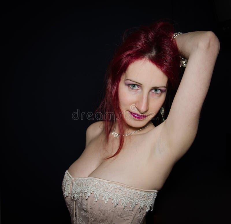 Αισθησιακή κόκκινη γυναίκα που εξετάζει τη κάμερα στοκ εικόνες