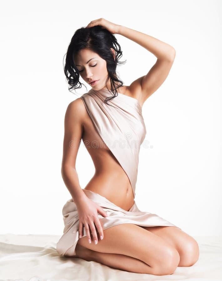 Αισθησιακή νέα γυναίκα με το όμορφο σώμα στο μπεζ μετάξι στοκ εικόνα με δικαίωμα ελεύθερης χρήσης
