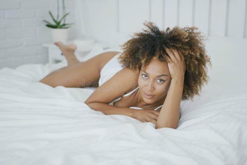 Αισθησιακή πρότυπη τοποθέτηση στο κρεβάτι στοκ φωτογραφίες