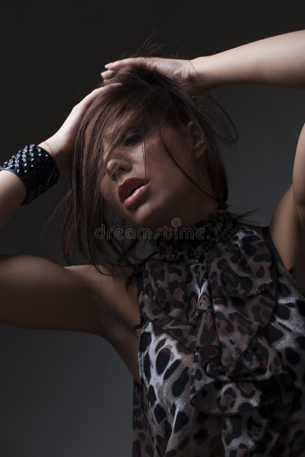 Αισθησιακή όμορφη νέα γυναίκα στη φούστα, σκοτεινό υπόβαθρο στοκ εικόνες