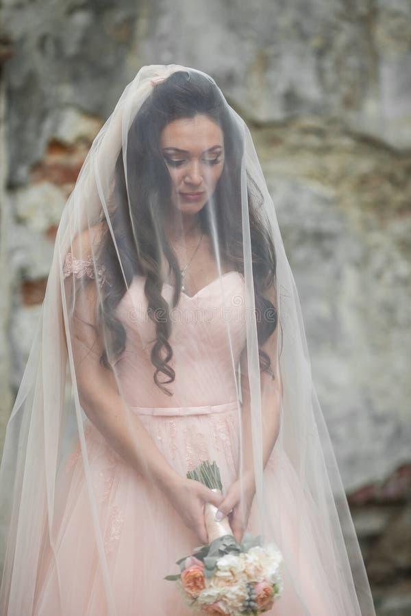 Αισθησιακή όμορφη νύφη brunette που κρατά μια ανθοδέσμη και που κρύβει τα Η.Ε στοκ φωτογραφία με δικαίωμα ελεύθερης χρήσης