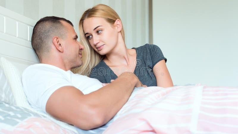 Αισθησιακό ζεύγος στην κρεβατοκάμαρά τους που εξετάζει στοργικά το ένα το άλλο, έννοια φύλων στοκ φωτογραφία